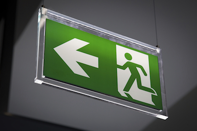 Emergency exit sign above a black doorway by CSS